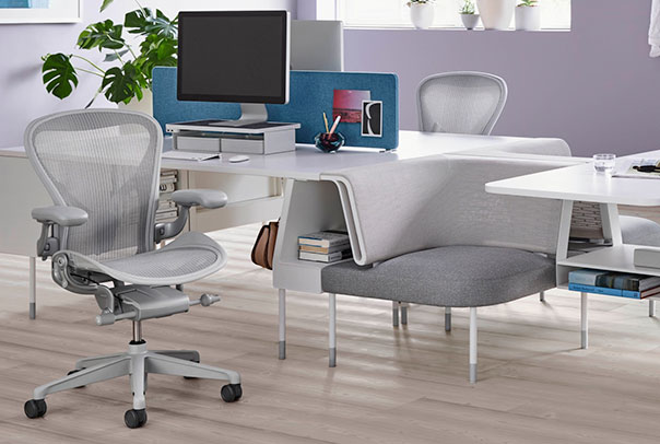 Neutral office with greay ergonomic desk chairs and white desks